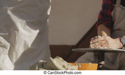 Woman carefully knead big piece of clay on pottery wheel....