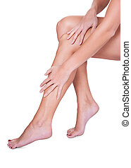 Woman caressing her silky smooth legs - Cropped view image...