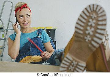 Woman carpenter at workbench talking on smartphone