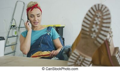 Woman carpenter at workbench talking on smartphone -...