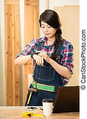 woman carpenter checking her smartwatch