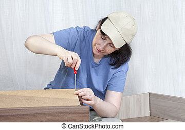 Woman carpenter screwing screw in wooden frame nightstand using screwdriver.