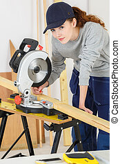 woman carpenter using circular saw selective focus depth of field