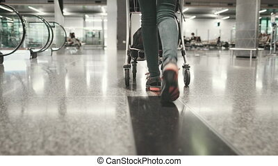 Woman Carry Luggage Cart Walk at Airport Terminal. Tracking Shot of Girl Legs in Trainers. Female Traveler Pushing Trolley with Baggage Forward to Boarding Gate. Footage Shot in 4K