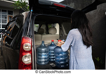 woman carrying a gallon of water put in car trunk