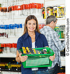 Woman Carrying Basket Full Of Tools In Store