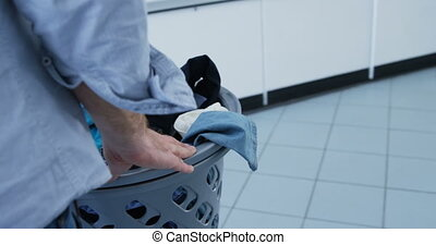Woman carrying clothes in basket trolley at laundromat 4k -...