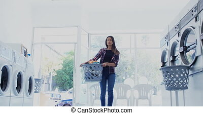 Woman carrying clothes in laundry basket at laundromat 4k -...