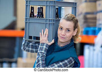 woman carrying crate of beers on her shoulder