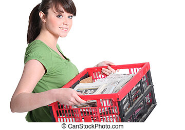 Woman carrying crate of newspapers to be recycled