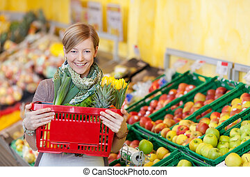 Woman Carrying Shopping Basket In Grocery Store - Portrait...