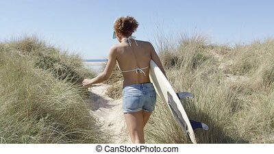 Woman carrying the surfboard - Back view of young woman with...