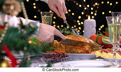 Woman carving roasted chicken on Christmas dinner - Woman...