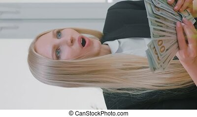 Female sitting at desk at workplace with computer holding in hands bundle of cash looking astonished at monitor, and throwing money in air. Video with Vertical Screen Orientation 9:16