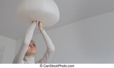 Woman changing CFL light bulb at home