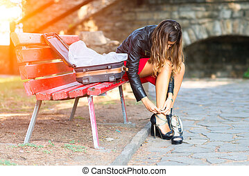 Woman changing shoes on a bench