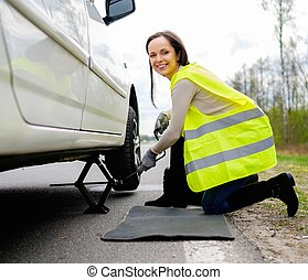 Woman changing wheel on a roadside