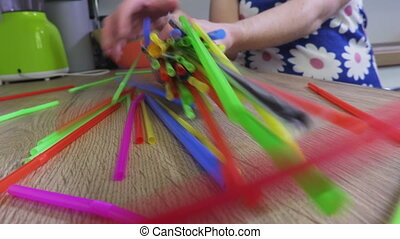 Woman chaotic mixing colorful plastic straws. Plastic, pollution concept