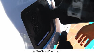 Woman charging electric car at charging station 4k -...