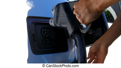 Woman charging electric car at charging station 4k - Close-...