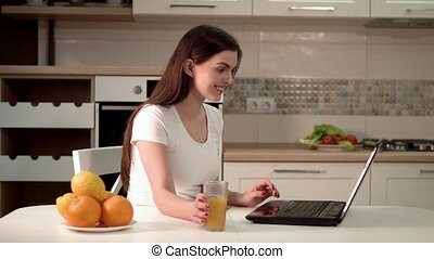 Woman Chats Happily on Laptop