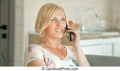 Woman Chats on Phone - Pretty blond woman chatting on phone...