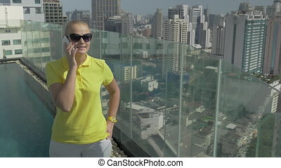 Woman chatting on phone from the roof of high building. Bangkok, Thailand
