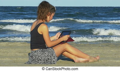 Woman chatting on social media on tablet pc by the sea