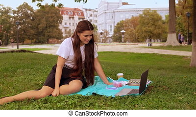 woman chatting online outdoors - happy student or...