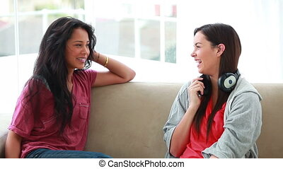 Woman chatting with a friend while holding headphones