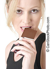 woman cheating on her diet - close up of blond woman about...