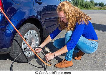 Woman checking air pressure of car tire - Female driver...