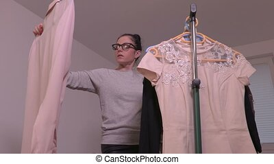 Woman checking clothes and put back on the rack
