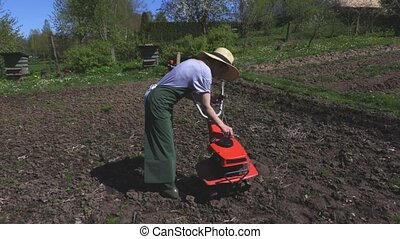 Woman checking cultivator oil level