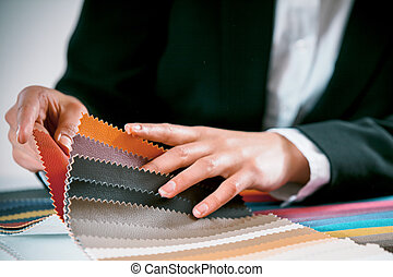 Woman checking fabric color swatches - Close up view of the...
