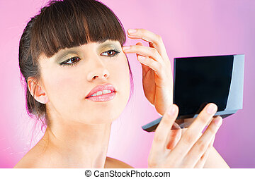 woman checking face skin in mirror