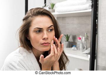 Woman checking face skin