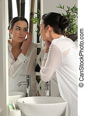 Woman checking her makeup in a bathroom mirror
