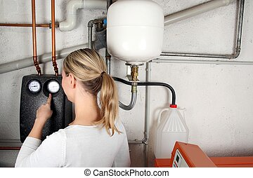 Woman checking instruments in the boiler room