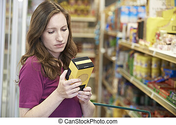 Woman Checking Labelling On Box In Supermarket