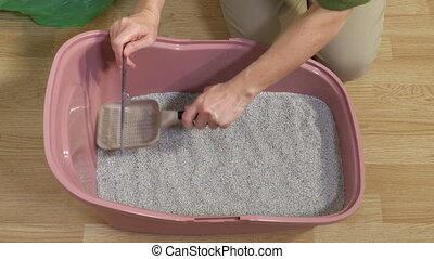 Woman checking level of clay sand in cat litter box