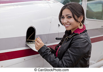 Woman checking oil in airplane