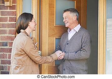 Woman Checking On Elderly Male Neighbor