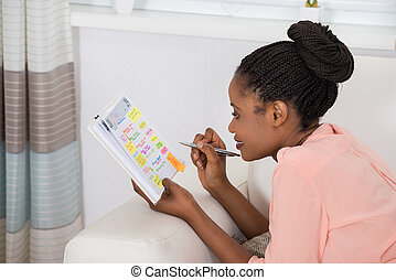 Woman Checking Schedule In Diary - Smiling Young African...