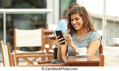 Woman checking smart phone in a bar