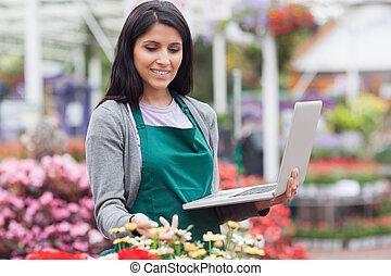 Woman checking stocks in garden center
