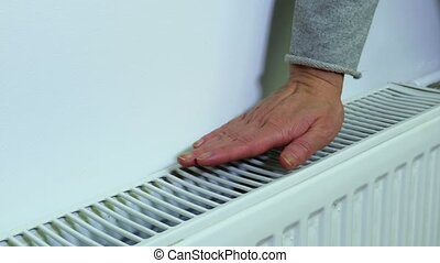 Woman checking temperature of heating radiator