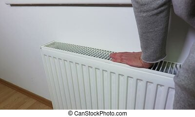 Woman checking the heating radiator