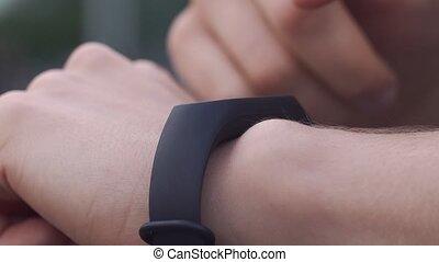 Woman checks data on her fitness bracelet.