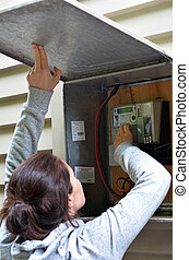Woman checks the electric meter.
